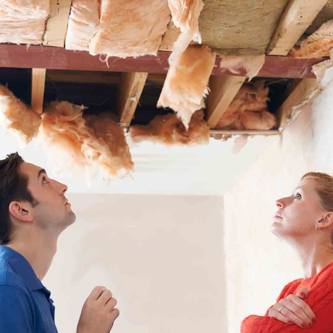 couple examining hole in their ceiling
