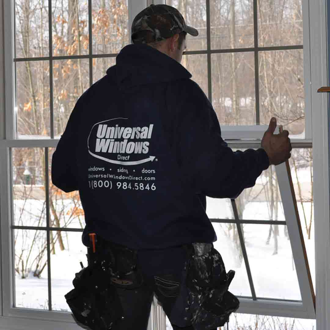 uwd worker installing bottom sash of new double hung window