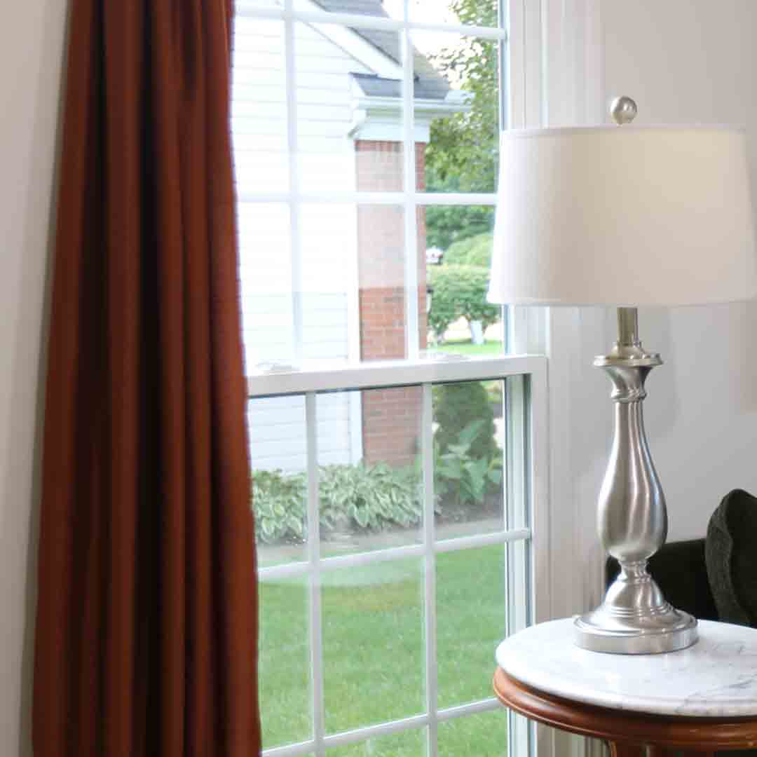 Lamp and table in front of double hung window with grids