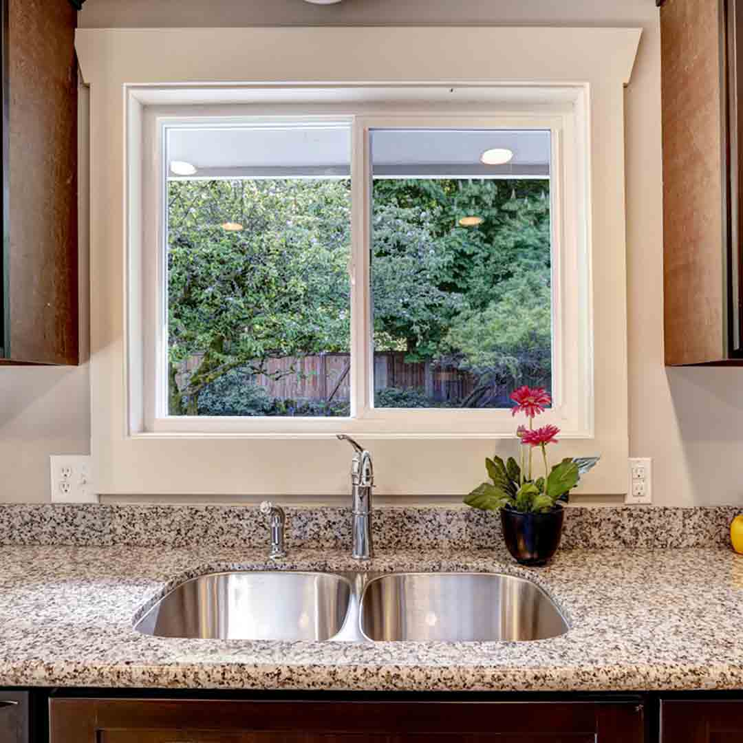 white vinyl slider window above kitchen sink