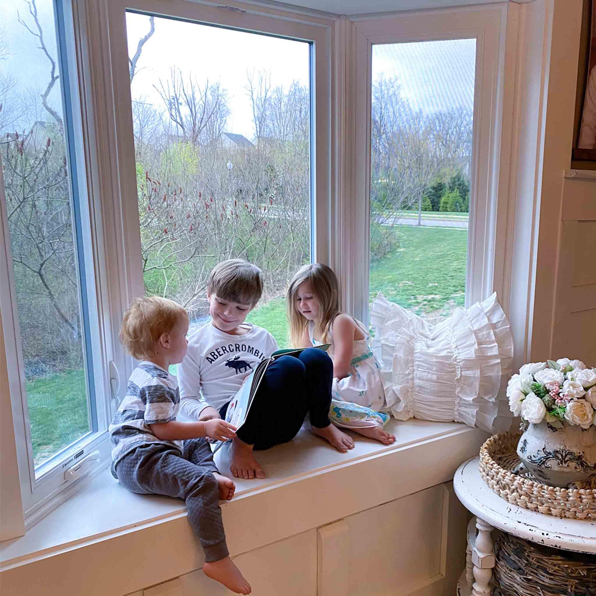 Kids sitting in bay window seat reading a book