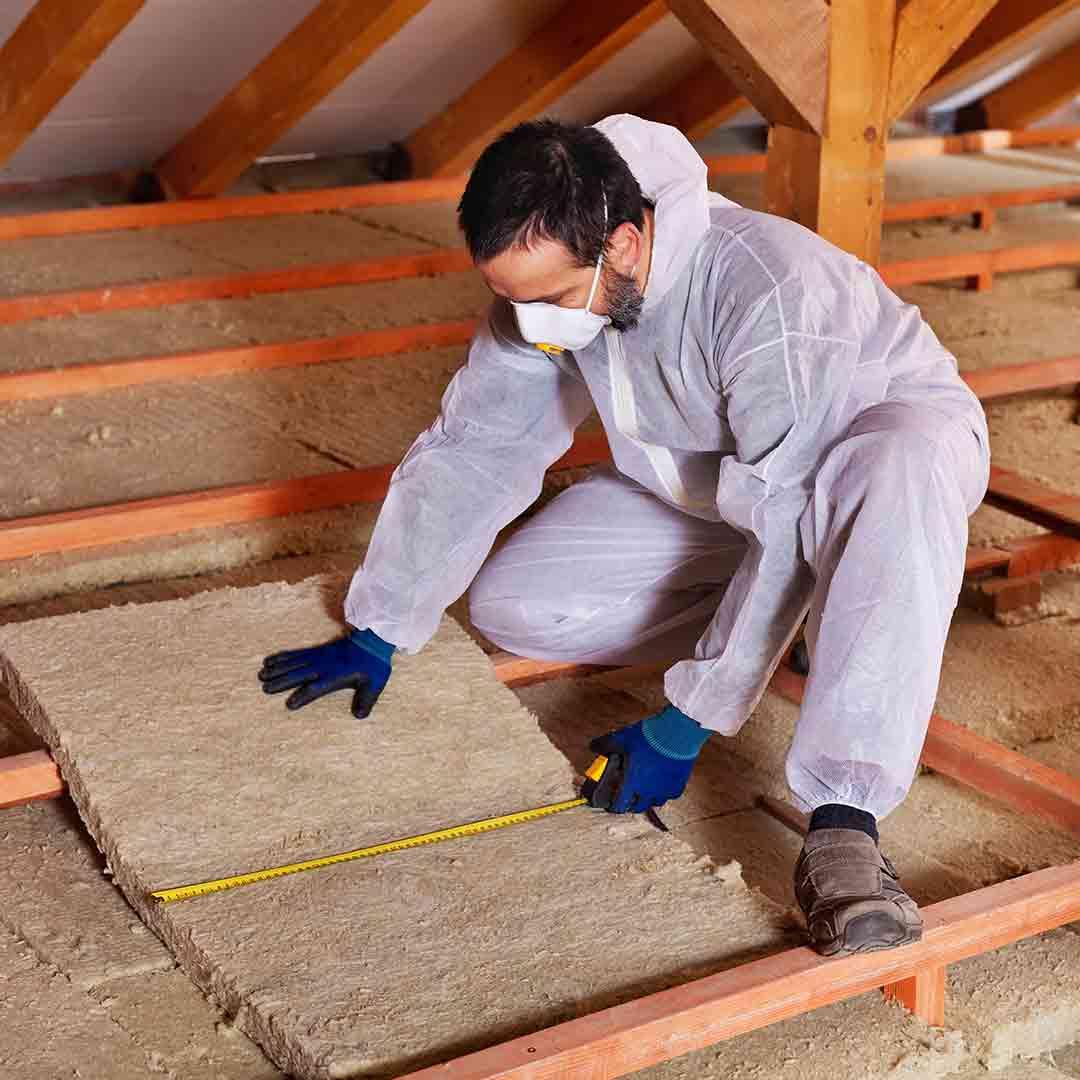 man laying attic insulation