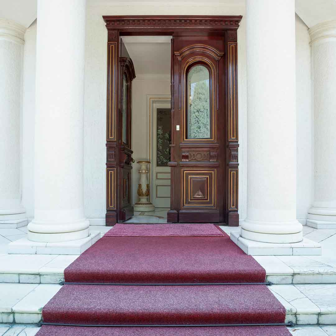 beautiful, ornate double front door, standing between two pillars