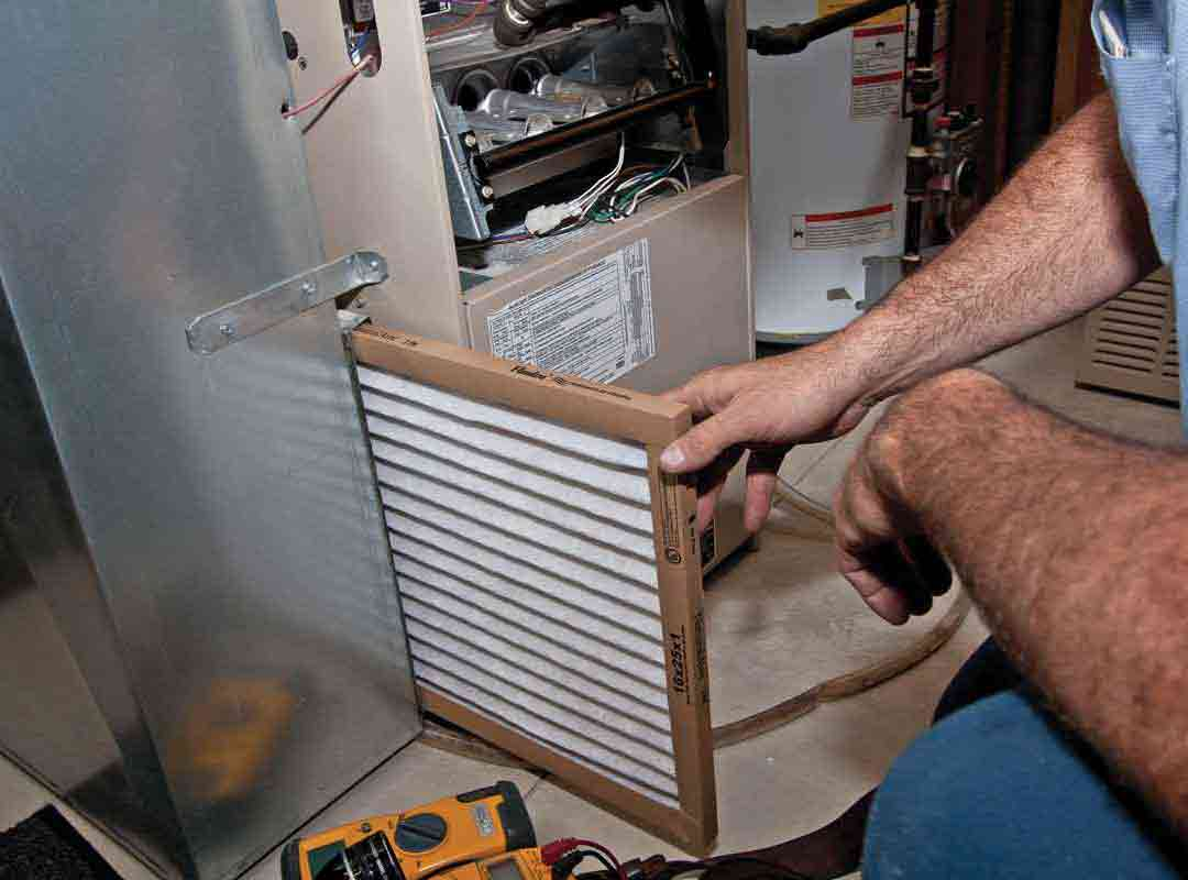 man replacing furnace filter