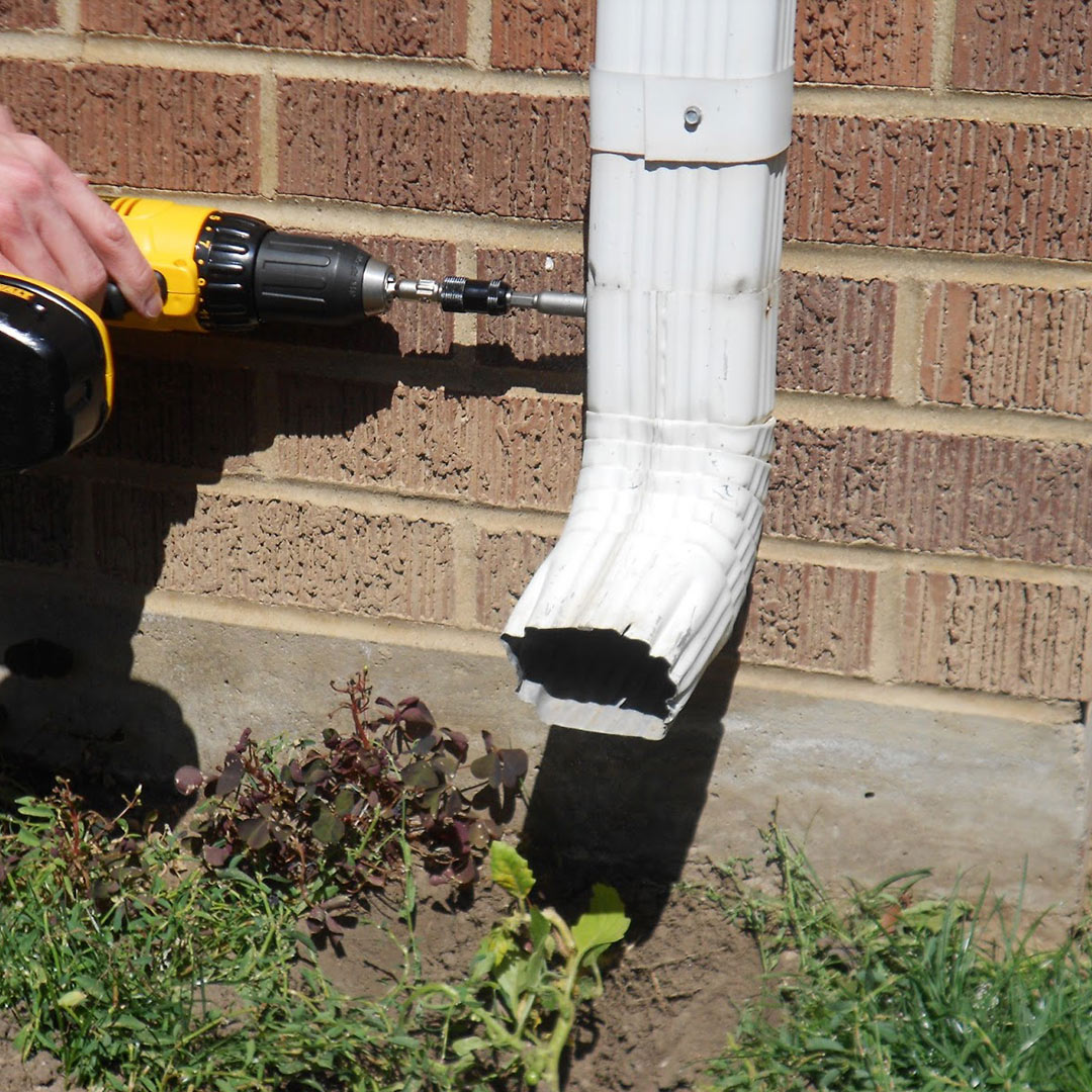 man drilling gutter downspout in place