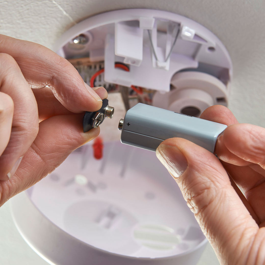 hands changing battery in smoke detector