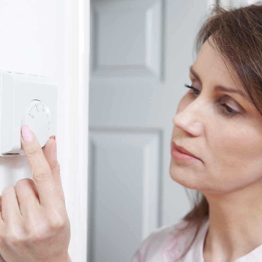 woman turns down thermostat