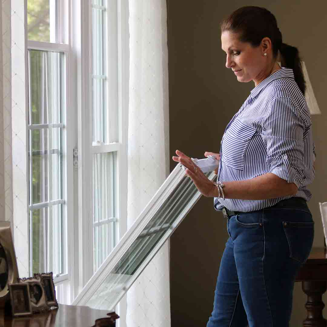 woman tilting-in a double hung window